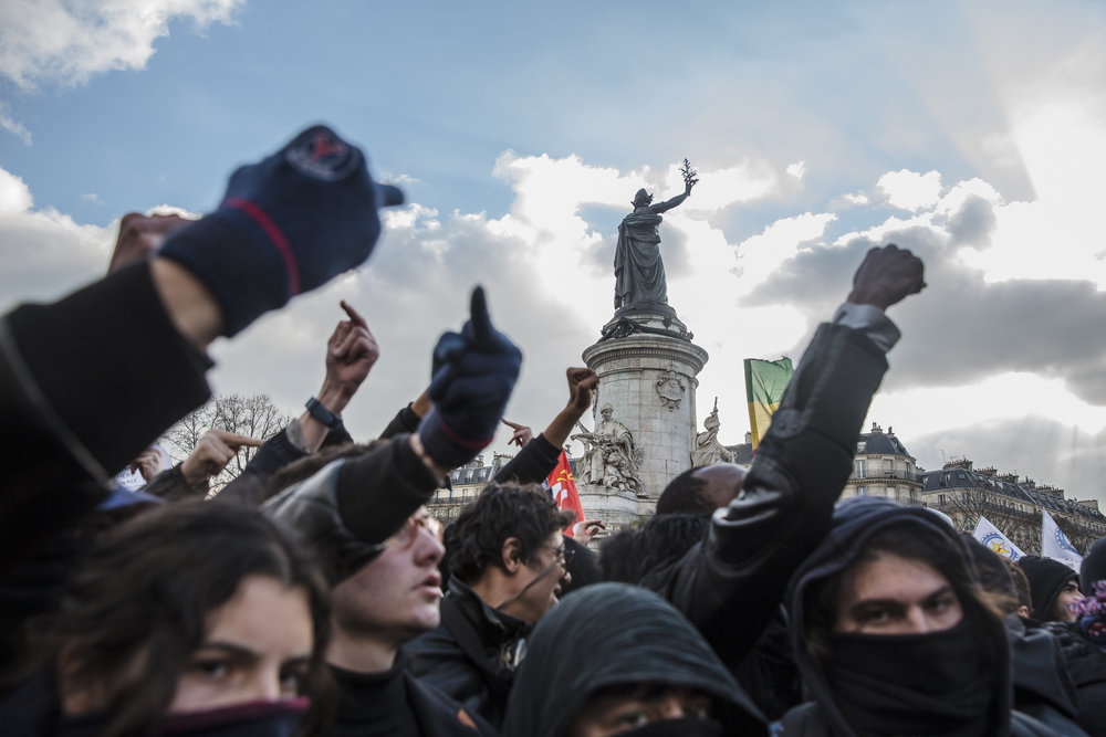 Anti facist 'black bloc' protestors raise their middle fingers in unison at a rally against police brutality as tensions begin to mount in Republique Paris, France on February 18, 2017.