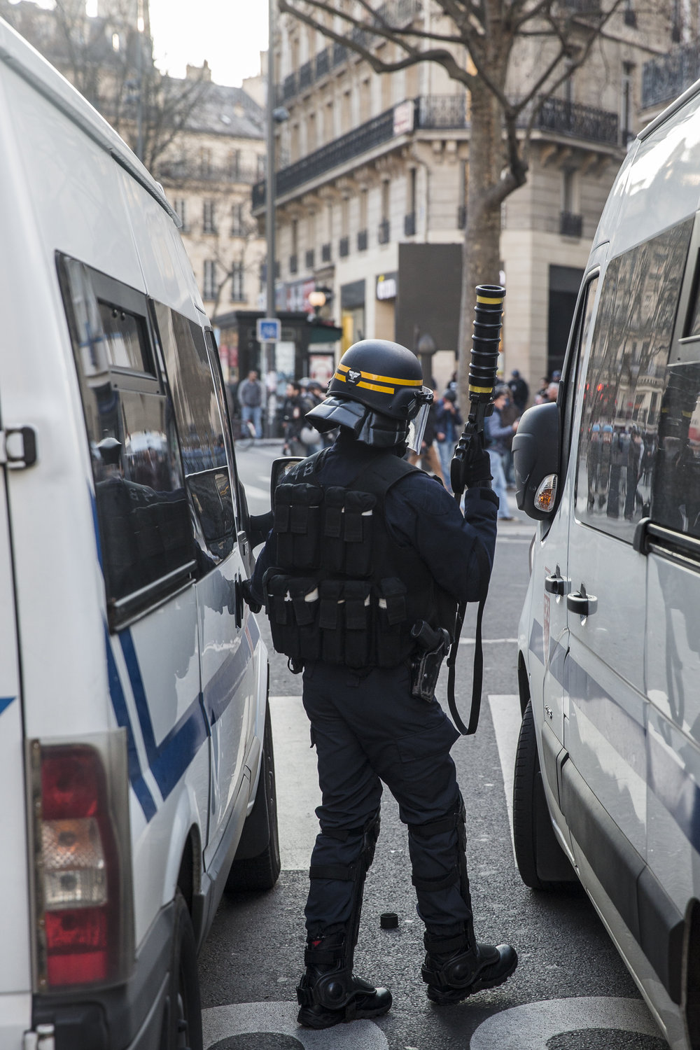 A police officer readies his riot gun as anti police brutality protests turn violent at Republique in Paris, France on February 18, 2017.