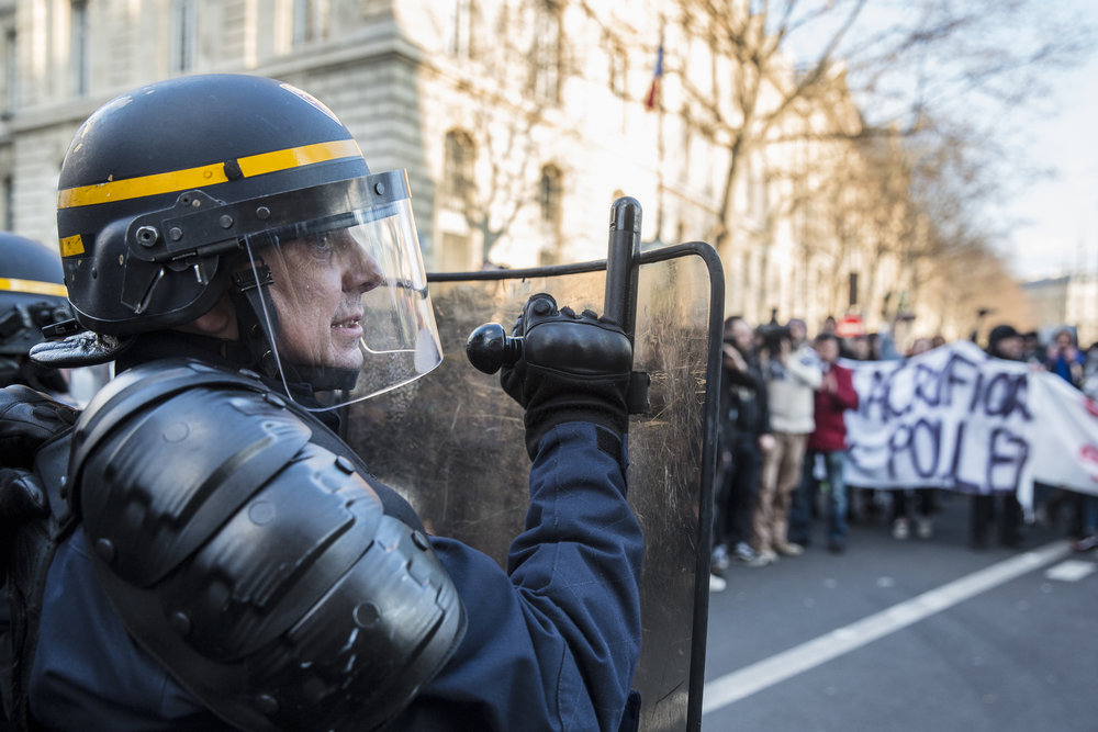 A member of Paris' riot squad police shields himself from debri being hurled toward a police barricade set up at the perimeter of Republique in Paris, France on February 18, 2017.