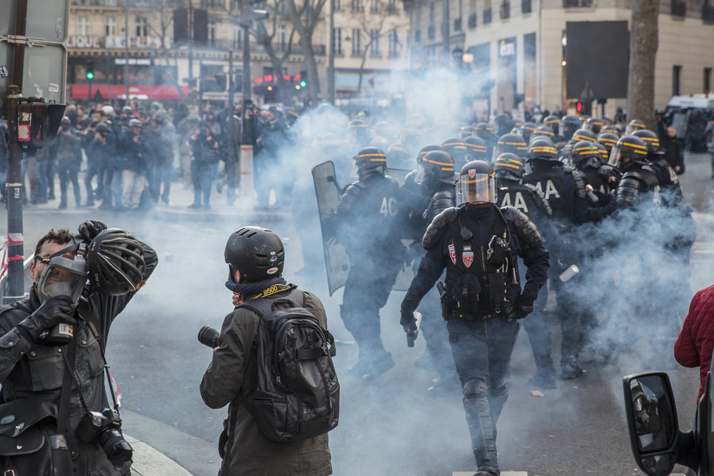 Riot squad police fire tear gas into the crowds of protestors and shield themselves from as protests turned violent at a rally against police brutality at Republique in Paris on February 18, 2017.