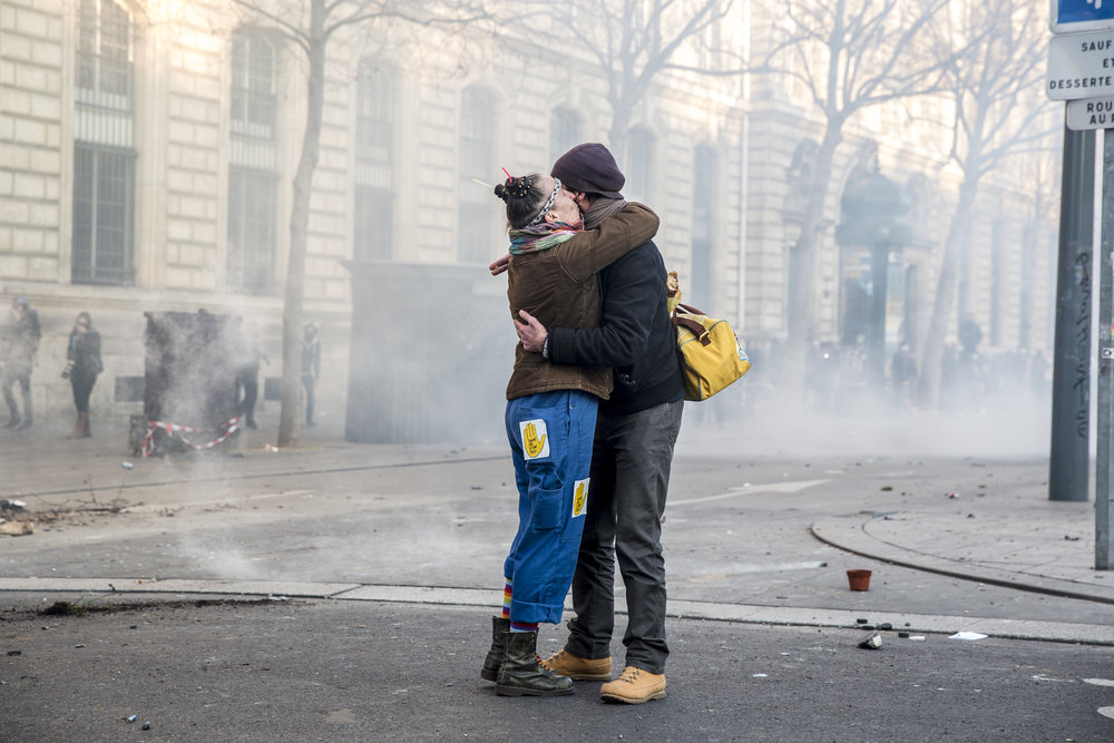 Two demonstrators embrace amid a cloud of tear gas as protestors clashed with police at Republique, in Paris, France on February 18, 2017.