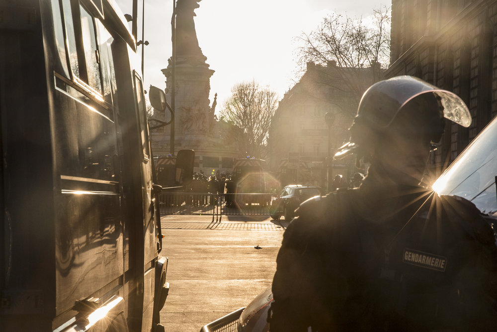 The sun begins to set as squad officer guards the perimeter around Republique Square as demonstrators began to clash with police inside, in Paris, France on February 18, 2017.