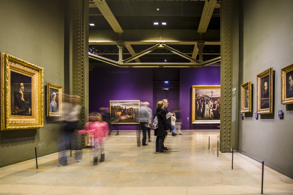 Visitors of the Musee D'Orsay go in and out of the gallery of Gustave Courbet, in Paris, France.