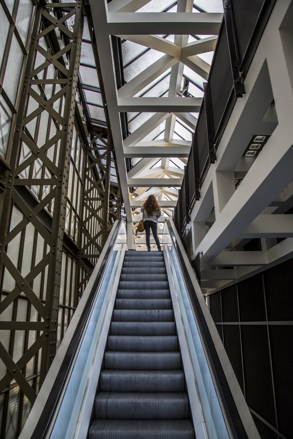 A woman ascends to the fifth floor on an escalator at the Musee D'Orsay in Paris, France.