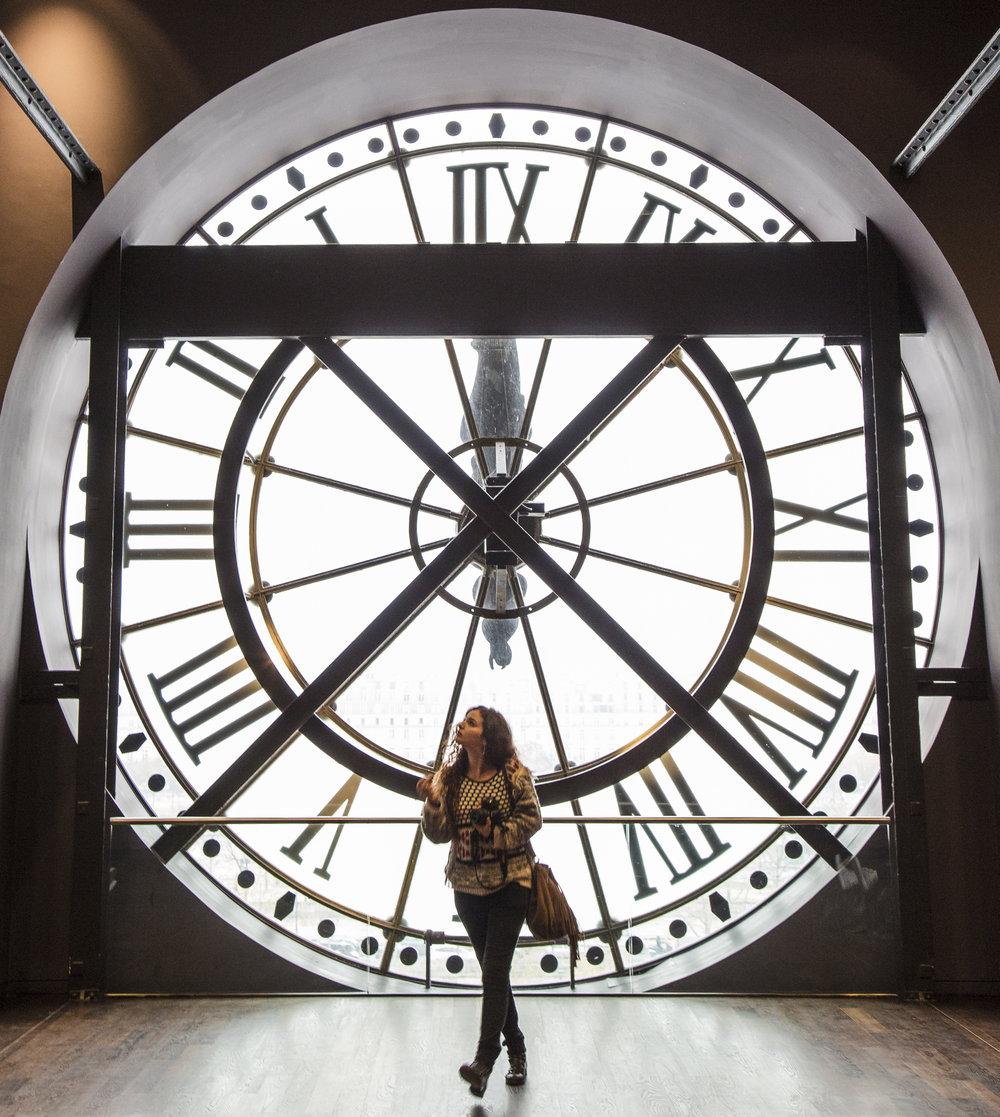 The clock strikes high noon as a museum goer makes her way past it into The Impressionist Gallery, in Paris, France.