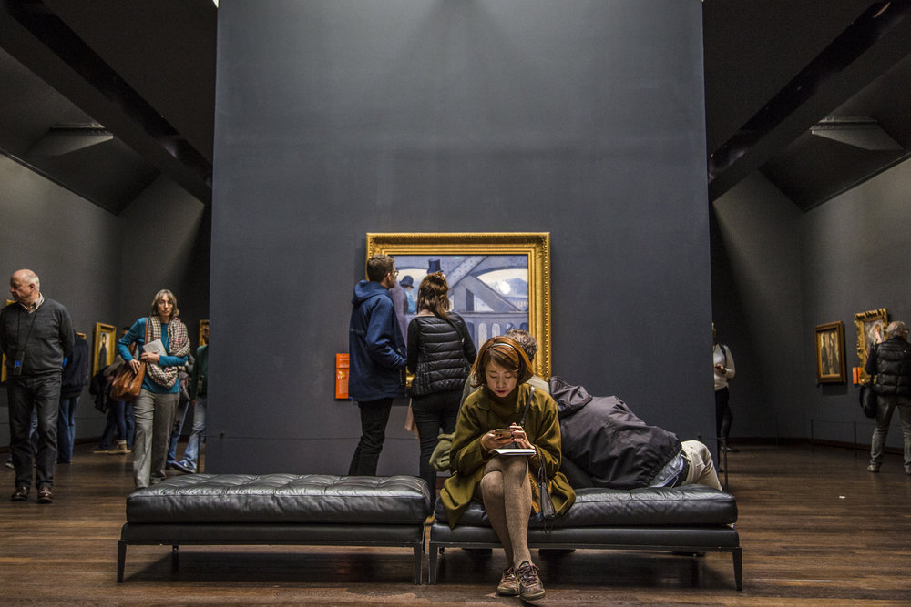 Visitors of the Musee D'Orsay relax on a bench in The Impressionist Gallery in Paris, France.