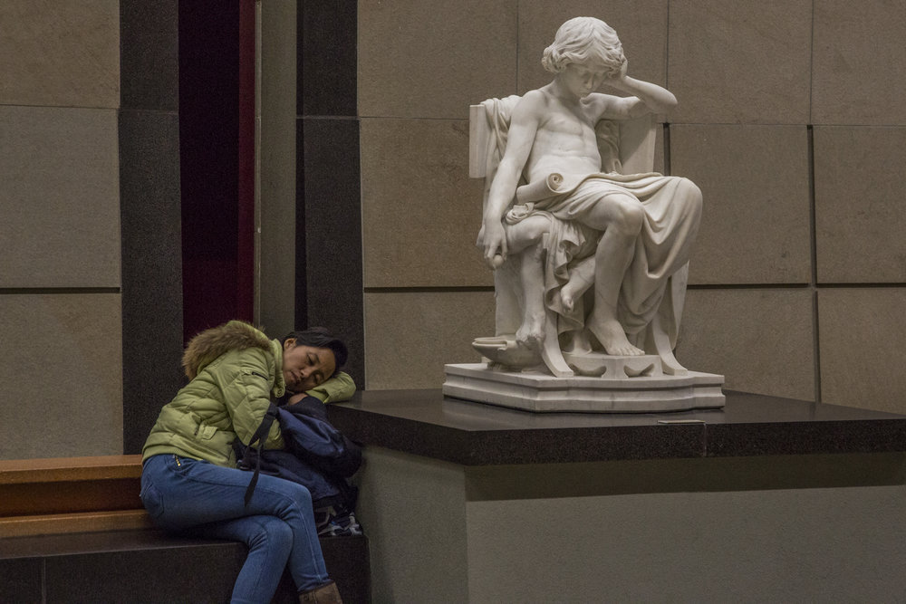 A woman dozes off in the Main Hall of the Musee D'Orsay in Paris, France.