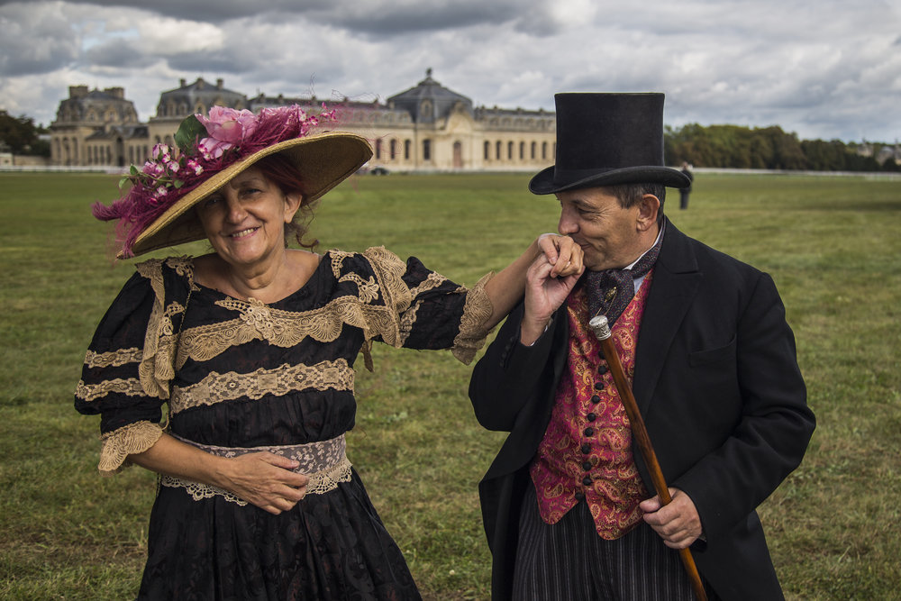 Spectators decked out in full Victorian age regalia share a tender moment at the Chantilly Racecourse in Chantilly, France on Oct. 2, 2016.