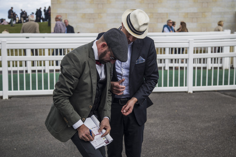 Two race attendees consult their racing guide before placing their bets at the Qatar Prix de L'Arc de Triomphe, on Oct. 2 2016.