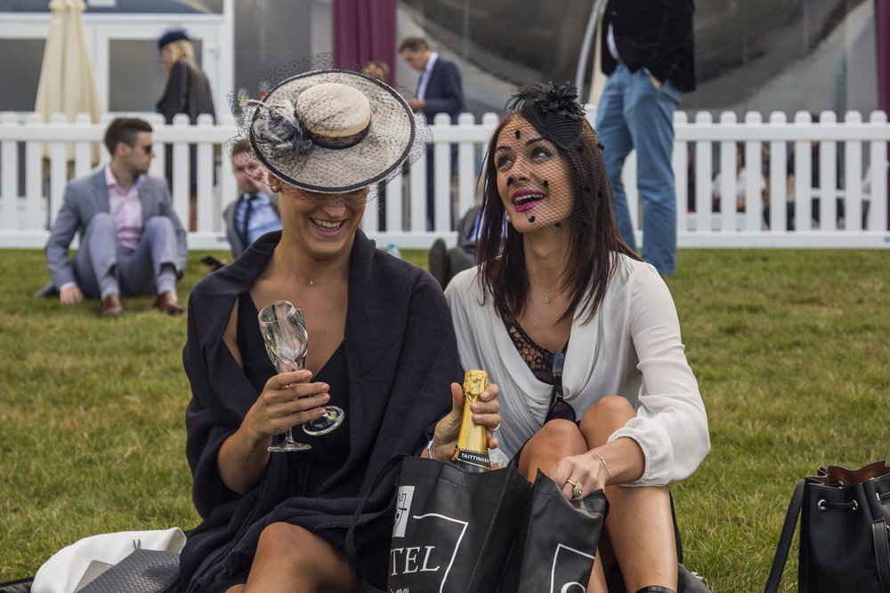Spectator's laugh together as they prepare to open a bottle of Champagne on the lawn of the Chantilly racecourse in Chantilly, France on Oct. 2, 2016.