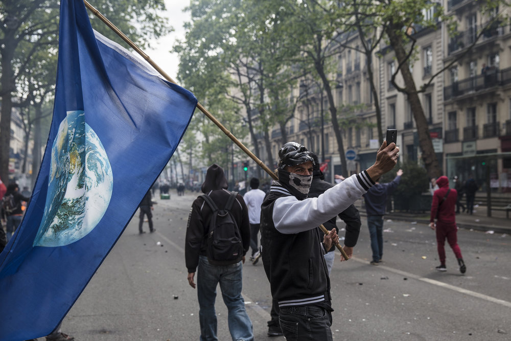 A demonstrator poses for a selfie before joining his comrades as protests descended into riots on May Day in Paris, France on May 1, 2017.