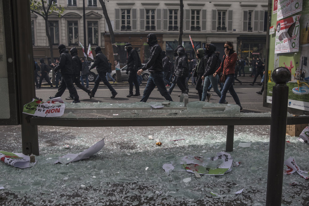 Members of the anti fascist black bloc march past a busted out bus stop window as riots broke out in front of Bastille on International Worker's Day in Paris, France on May 1, 2017.