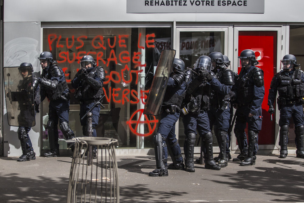 Police get in formation front of anarchist graffitti on Boulevard Beaumarchais as protests turned violent during the Mayday demontrations near Bastille in Paris, France on May 1, 2017.