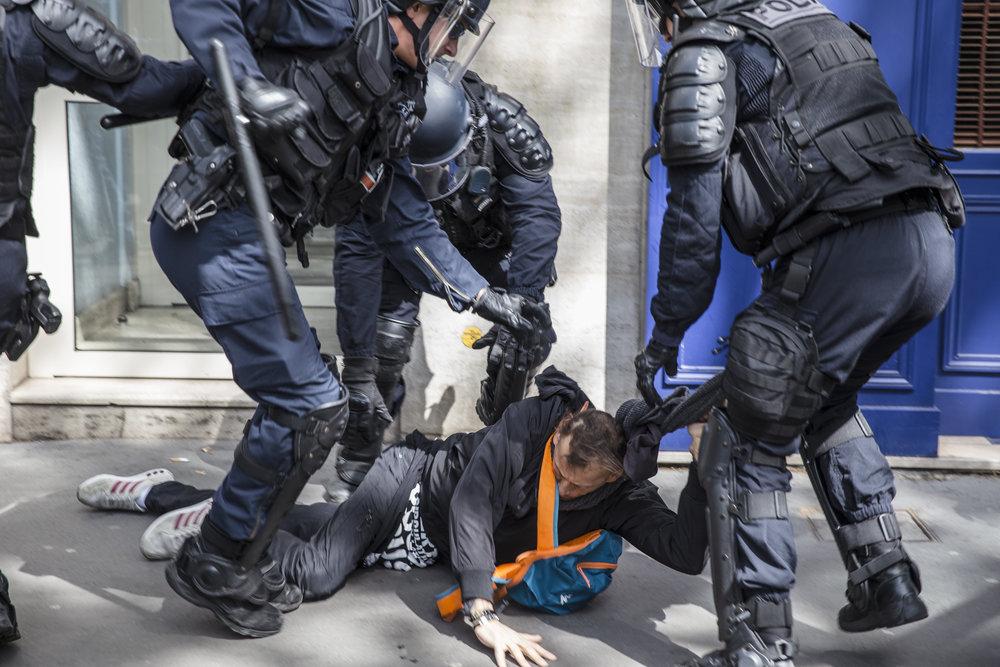 Police beat a protestor during the May Day protests. This is one of the last frames took before an officer shot me in the head with a flash bang grenade, used for dispersing crowds, at close range.
