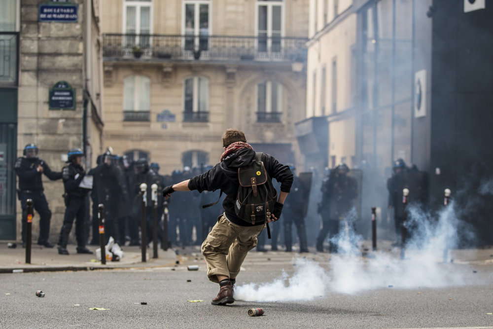 A protestor kicks a tear gas canister back at the police during clashes between anti fascist demonstrators and police turned violent during the Mayday protests in Paris, France.
