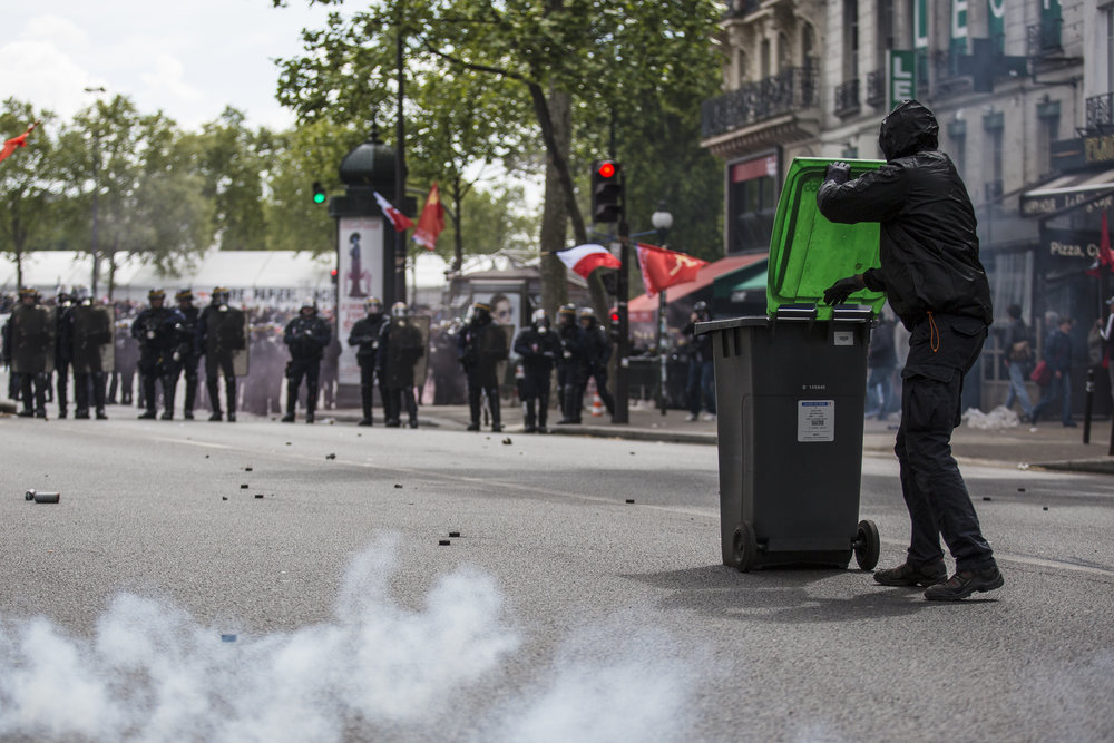 An antifacist demonstrator pushes a trash can filled with explosives toward  a police position in front of Bastille as protests turned violent and demonstrators clashed with Police in Paris, France.