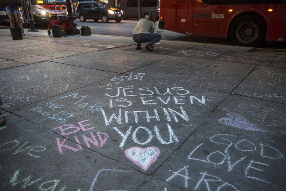 Members of the Western Presbyterian Church draw slogans of love and unity outside the Foggy Bottom metro station where the Unite The Right 2 rally is scheduled to begin the next day.