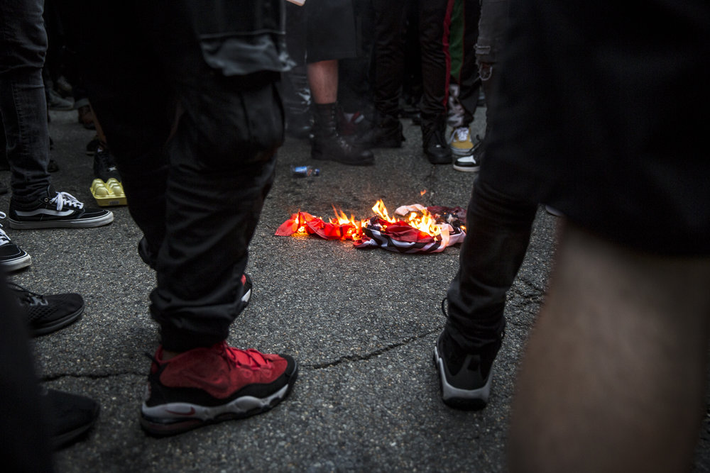 Anti fascist demonstrators set fire to a confederate flag outside the entrance to Lafayette Park while protesting against the Unite The Right 2 rally.