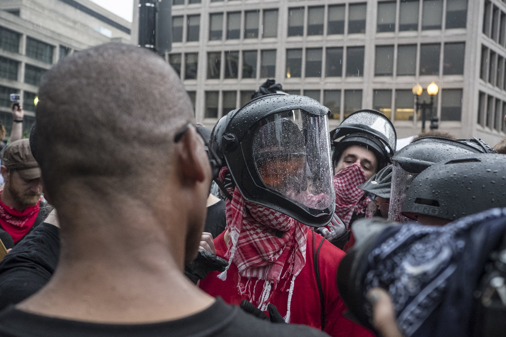 Tensions flare between different factions of protestors at the police barricade at the entrance of Lafayette Park.