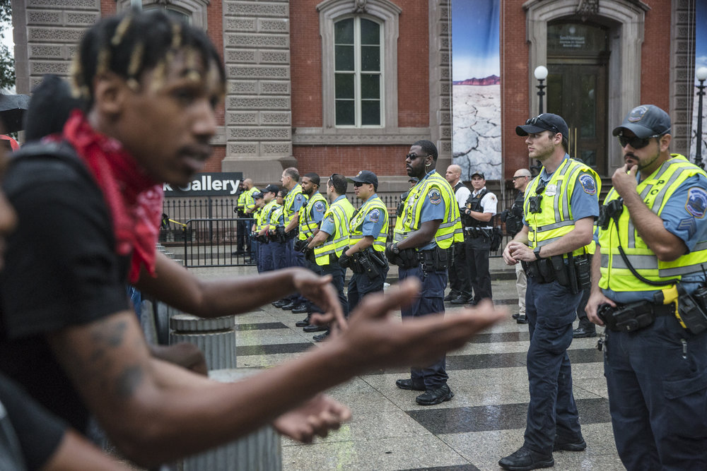 A protestor tries speaking with police at the barricade outside Lafayette Park as crowds of protestors disperse after learning the Unite The Right 2 rally had been shut down.