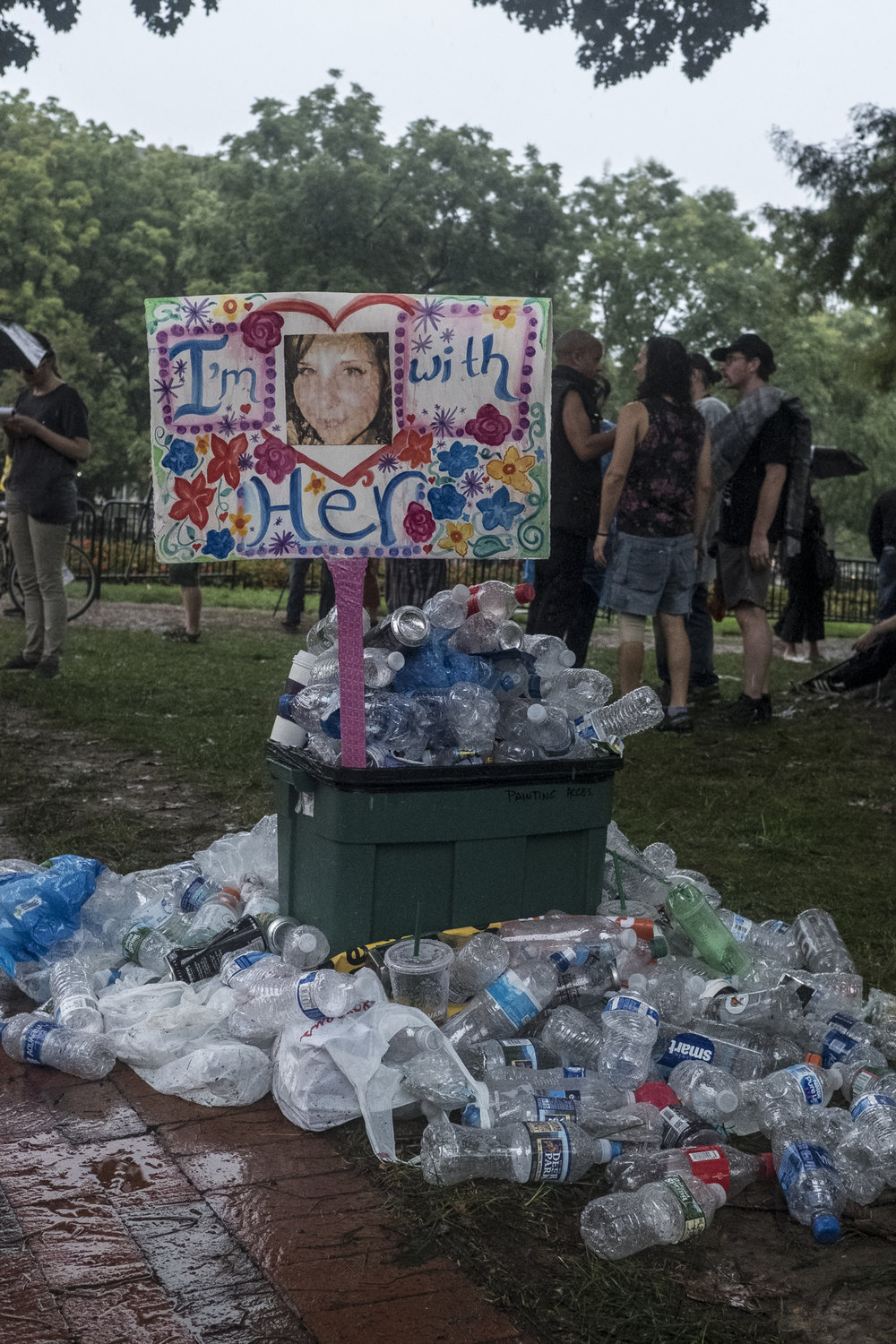 A protest sign with image of Heather Heyer who died during the Unite The Right rally in Charlottesville the year before stands among discarded plastic bottles in Lafayette Park.