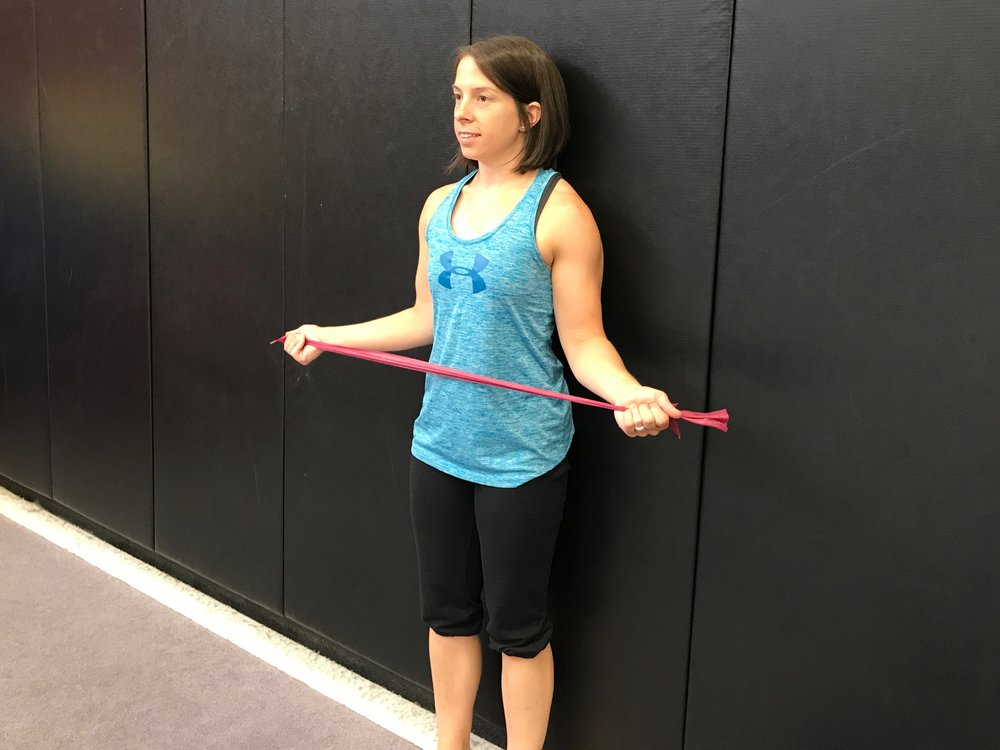 Exercise: Squeeze the shoulder blades together and twist the arms out. Then return to the starting position. (Be sure to keep the head neutral and body upright.) Be certain that the elbow remain bent and that the rotation is coming from the shoulders and not extension of the elbows.
