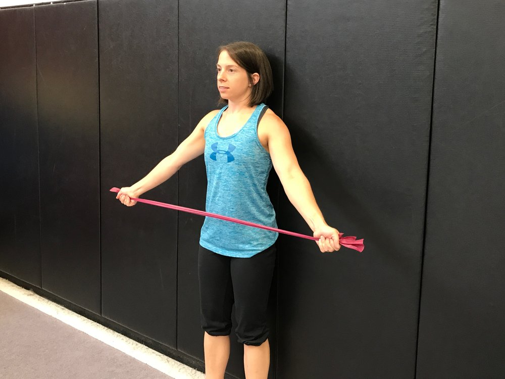 Exercise: Squeeze the shoulder blades together and raise the arms halfway up and out to the sides.Then return to the starting position. (Be sure to keep the head neutral and body upright.)