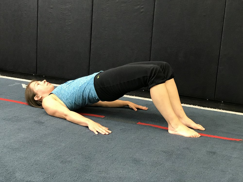 While keeping the core tight and back flat, lift the hips off the ground until there is a straight line between the knees, hips and shoulders. Hold this position for 5-15 seconds (while breathing) and then return to the starting position.