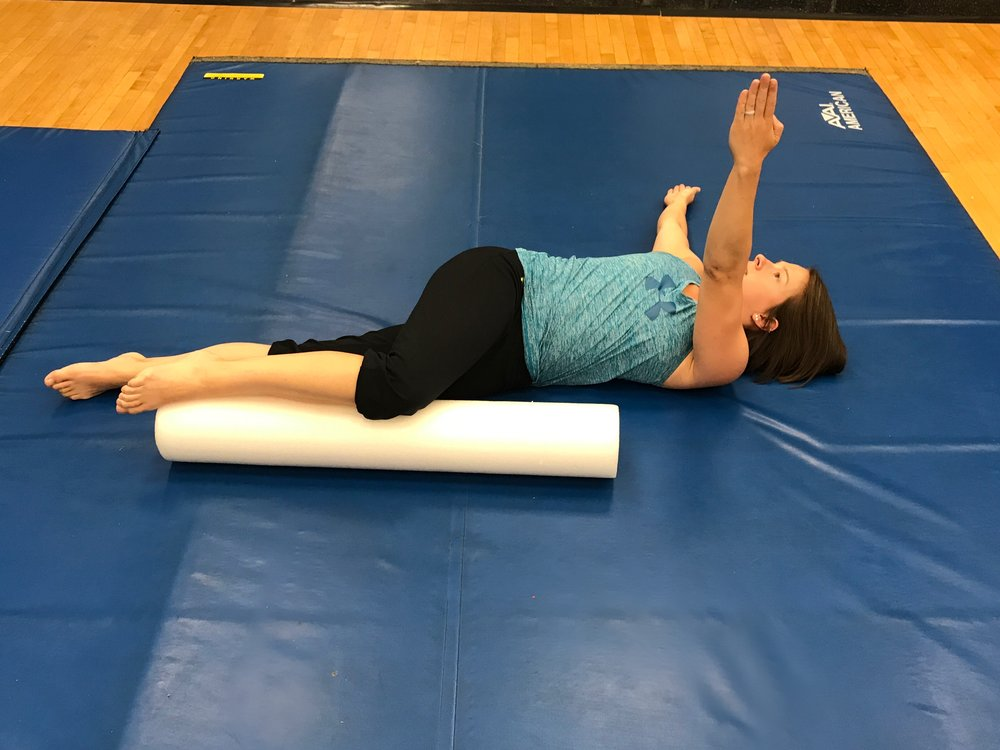 "Then, while still keeping the knee on the roll, rotate ""the box"" by twisting the upper back such that the top arm is now touching the floor behind you.  If you are able, reach the other arm up to the ceiling (think stretch/punch the shoulder forward) to increase the stretch."