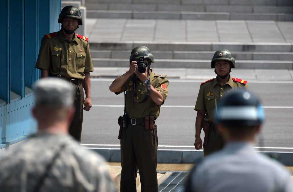 A North Korean soldier takes picture of an American soldier and a Korean military police officer on the DMZ line. Source: The Korea Times