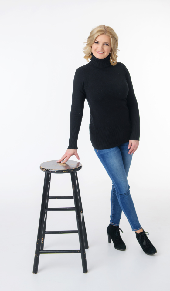 Corliss standing by a black stool
