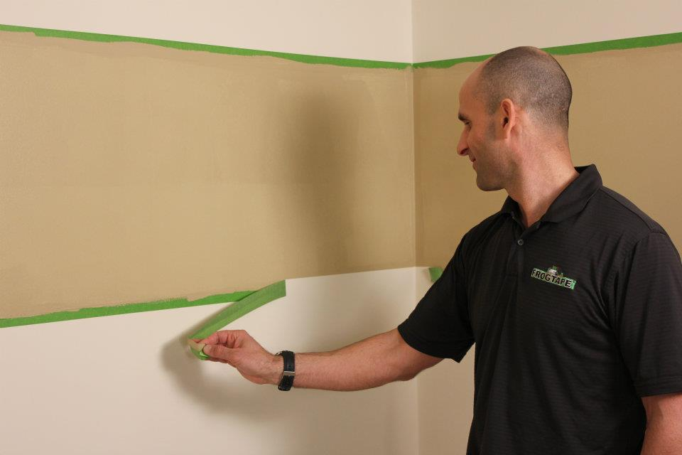 Dan Brady, a national spokesperson for Frog Tape, demonstrates its use in painting razor sharp lines inside a house.