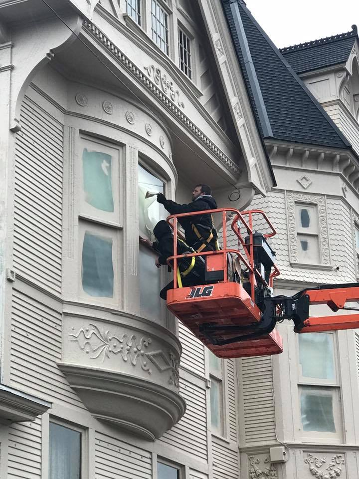 Painting exterior siding and trim on the Reynolds-Jonkoff building in Traverse City.