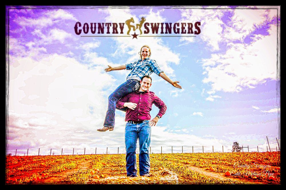 Picture of the Country Swingers. Man standing in a field with a woman sitting on his right shoulder spreading her arms.
