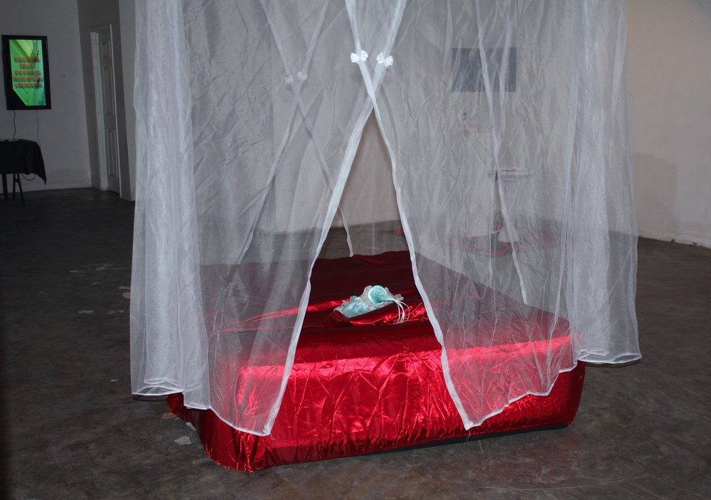 The Floating World (detail),  air mattress, satin sheets, mosquito net canopy, porcelain harlequin doll, 2017.
