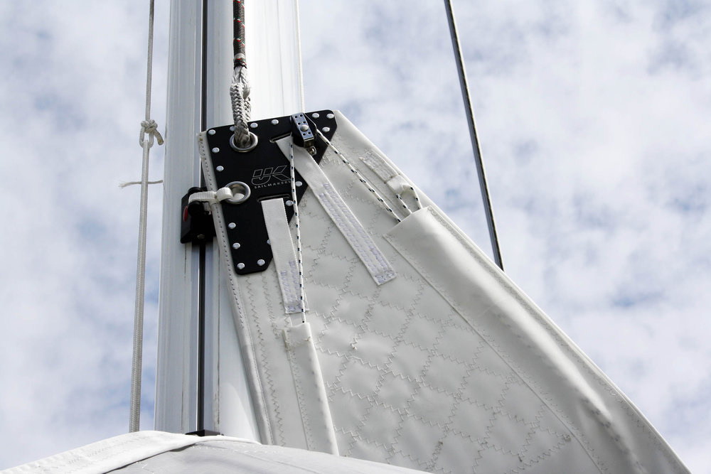 Notice the block on the back of the headboard that turns the leech line so that it comes down the luff to a cleat above the tack. An over the head leech line is needed on boats with high booms and it is the only leech line set up that can be adjusted when the back of the boom is not over the boat.