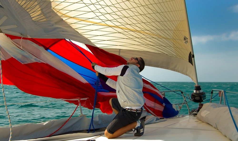 Using a dousing sock allows one person to douse the spinnaker. Without the sock several crew members would have to wrestle the sail to the deck. This shot shows one person lowering the sock on a 57-footer.