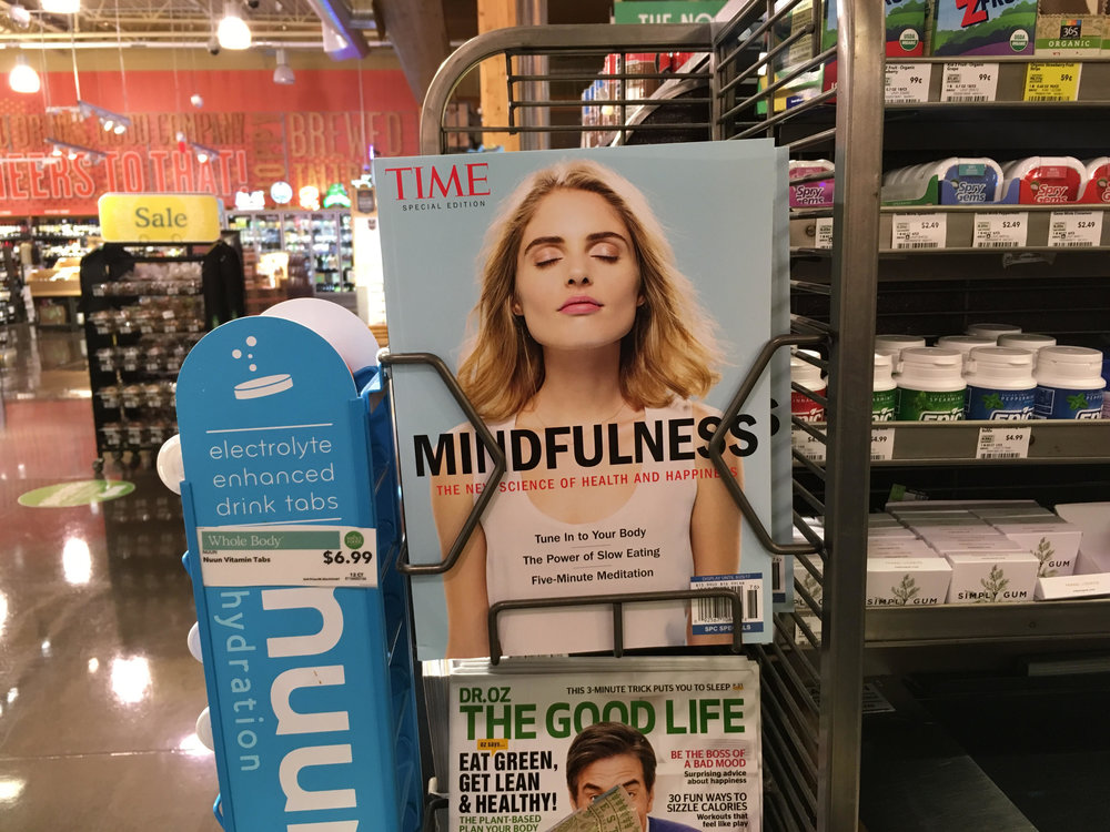 "Time magazine cover of a normative white woman with eyes closed and the words ""Mindfulness"" over her chest at a Whole Foods marketplace in Phoenix, AZ. June 2017"