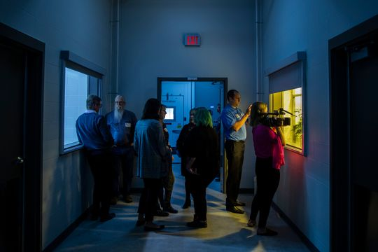 People crowd around the windows giving a view inside the cannabis growing rooms inside MedPharm's medical-marijuana production facility during an open house on Thursday, Nov. 1, 2018, in Des Moines. (Photo: Kelsey Kremer/The Register)