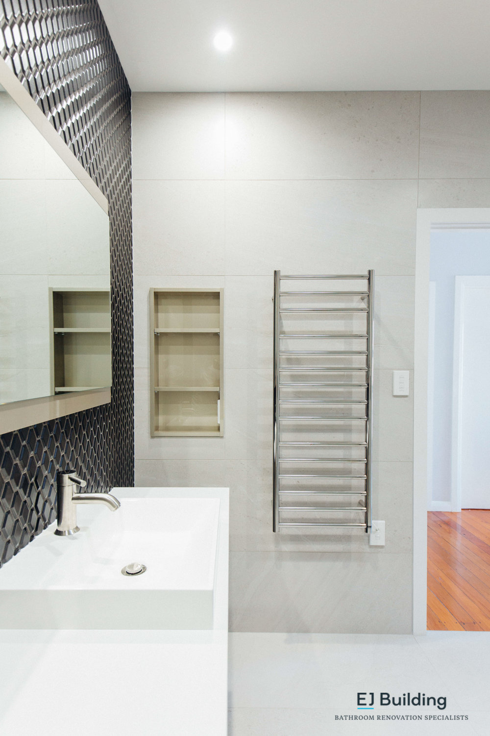 Ladder towel rail and recessed shelf in renovated bathroom.