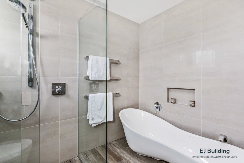 Ensuite renovation in Auckland showing tiled recessed shelf kept centre of the tile, with freestanding bath and tiled shower.