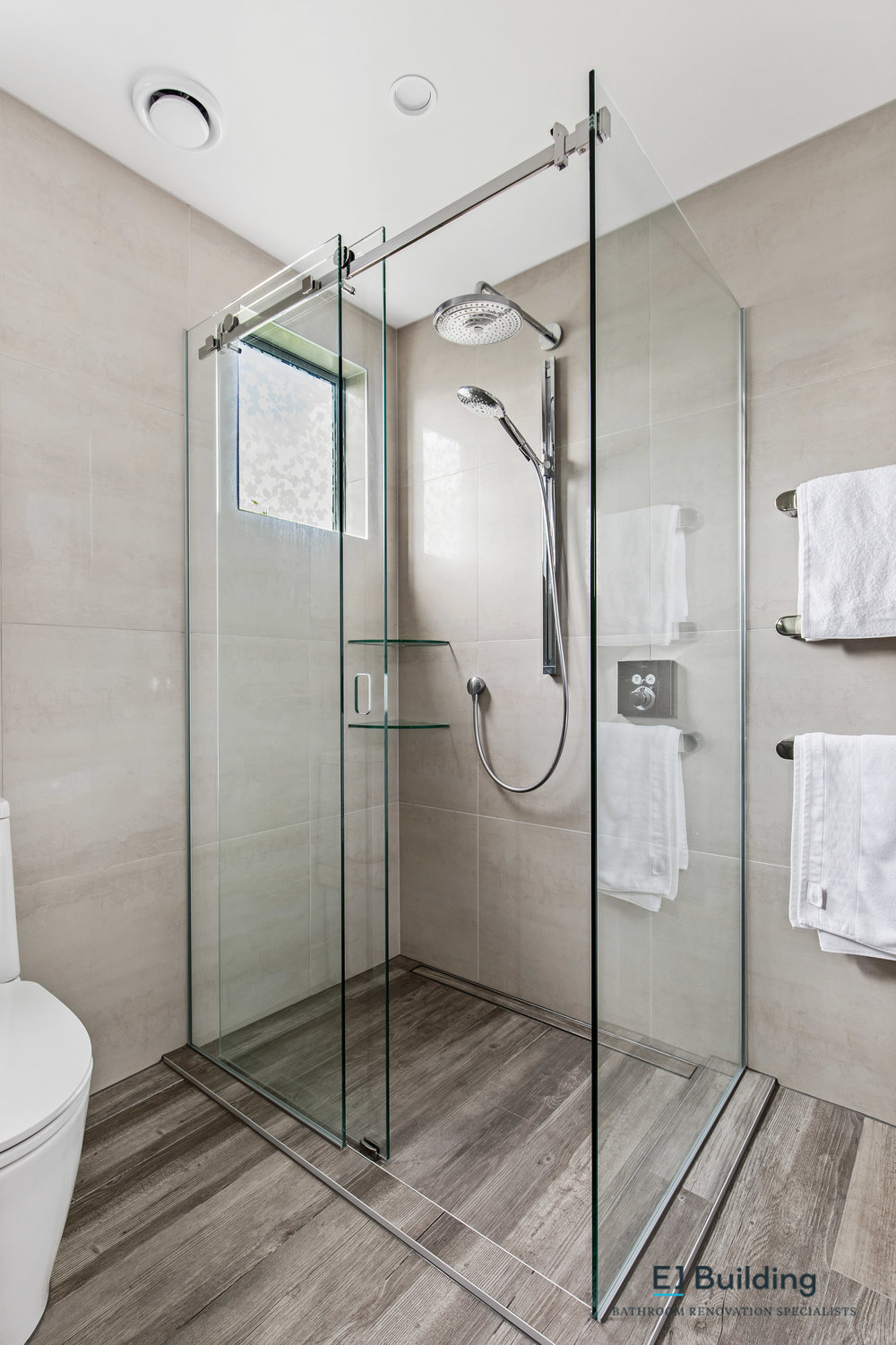 Interior designed bathroom in Auckland, showing tiled wet floor shower with custom frameless glass shower.