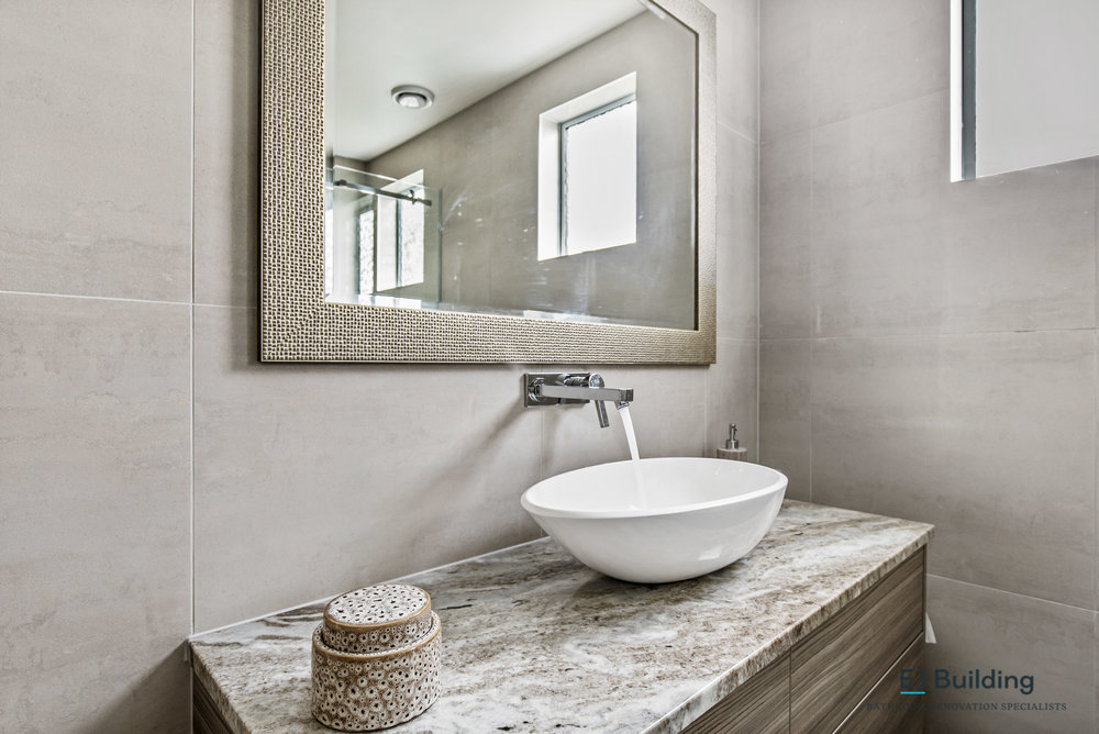 Interior bathroom design. Photo showing custom made vanity, stone top, wall mounted spout and mixer.
