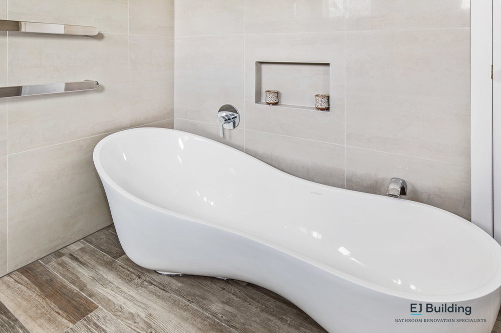 Auckland bathroom, showing timber looking tiles, freestanding bath with double wastes.