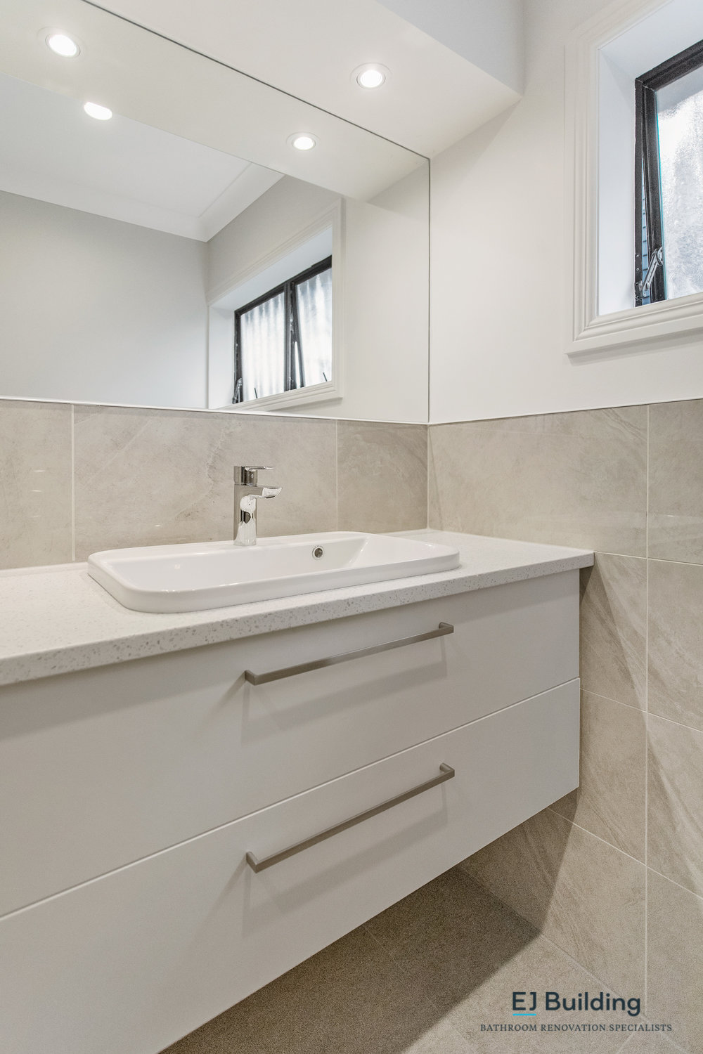 Ellerslie bathroom renovator Auckland. Bathroom vanity with stone vanity top. Bathroom mirror sitting on half high tiles.