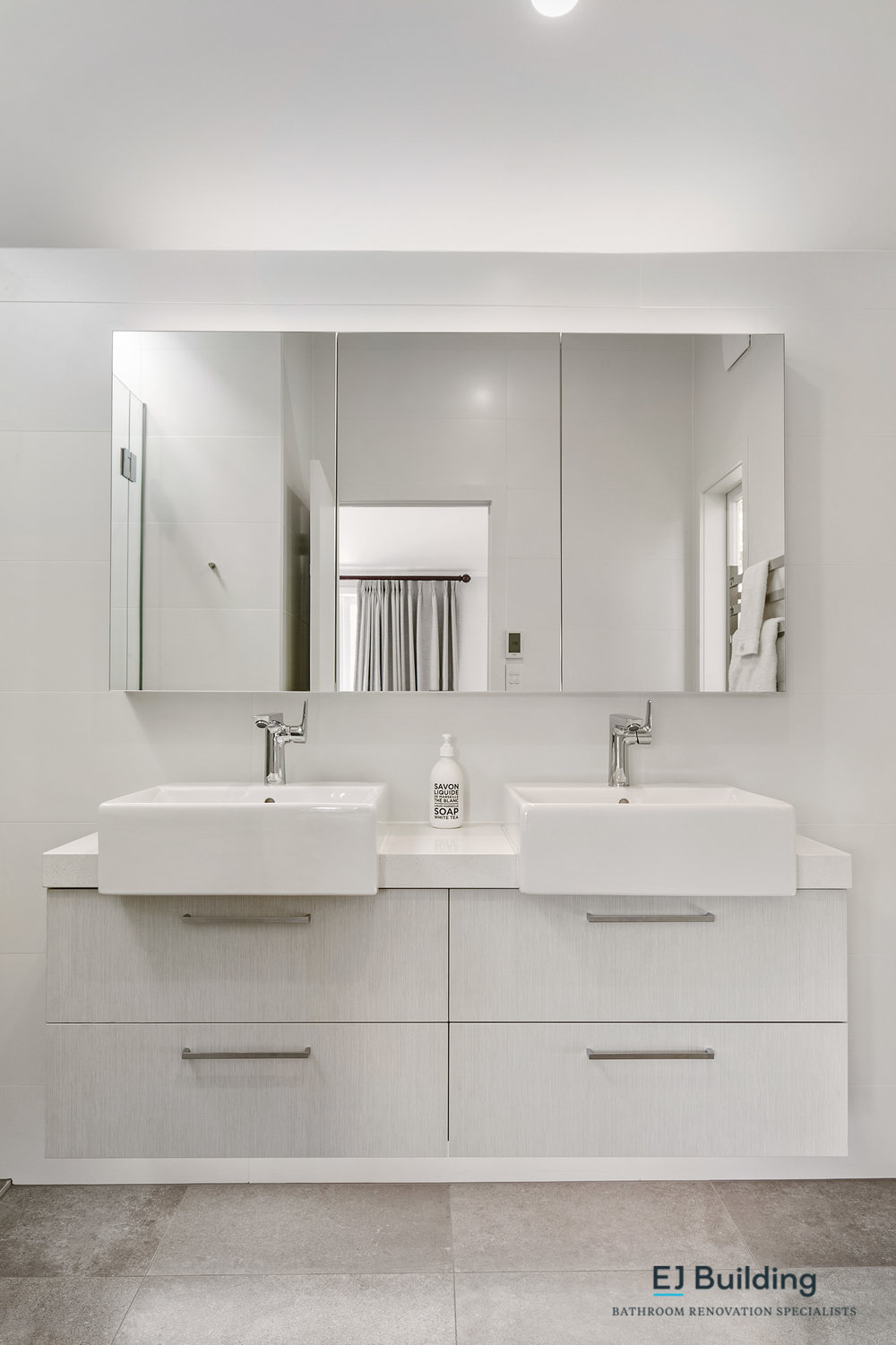 Ellerslie bathroom renovator Auckland. Wall hung vanity with LED lighting that turns on when you enter the ensuite. Mirror cabinet for additional bathroom storage. Under tiler floor heating for the new ensuite. Bathroom Renovation by E J Building Bathroom renovators In Auckland.