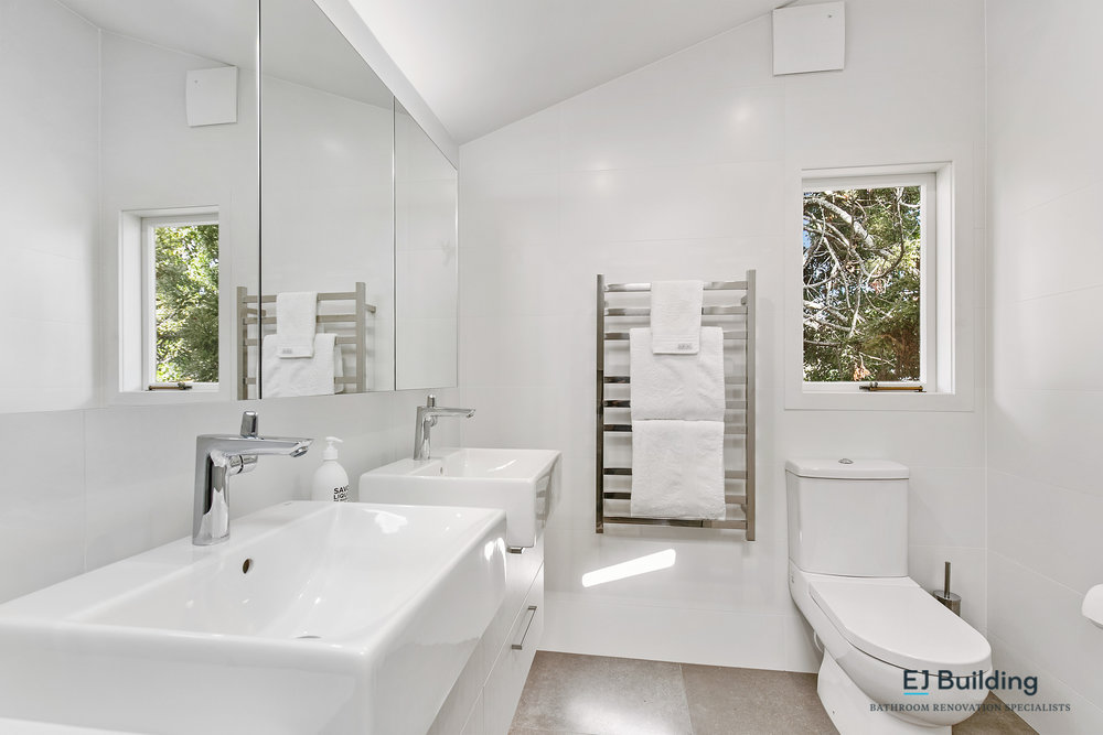 Ellerslie bathroom renovator Auckland. Nice bathroom layout with toilet under the window letting in natural light into the ensuite. His and hers basins in timber vanity. Bathroom Renovation by E J Building Bathroom renovators In Auckland.