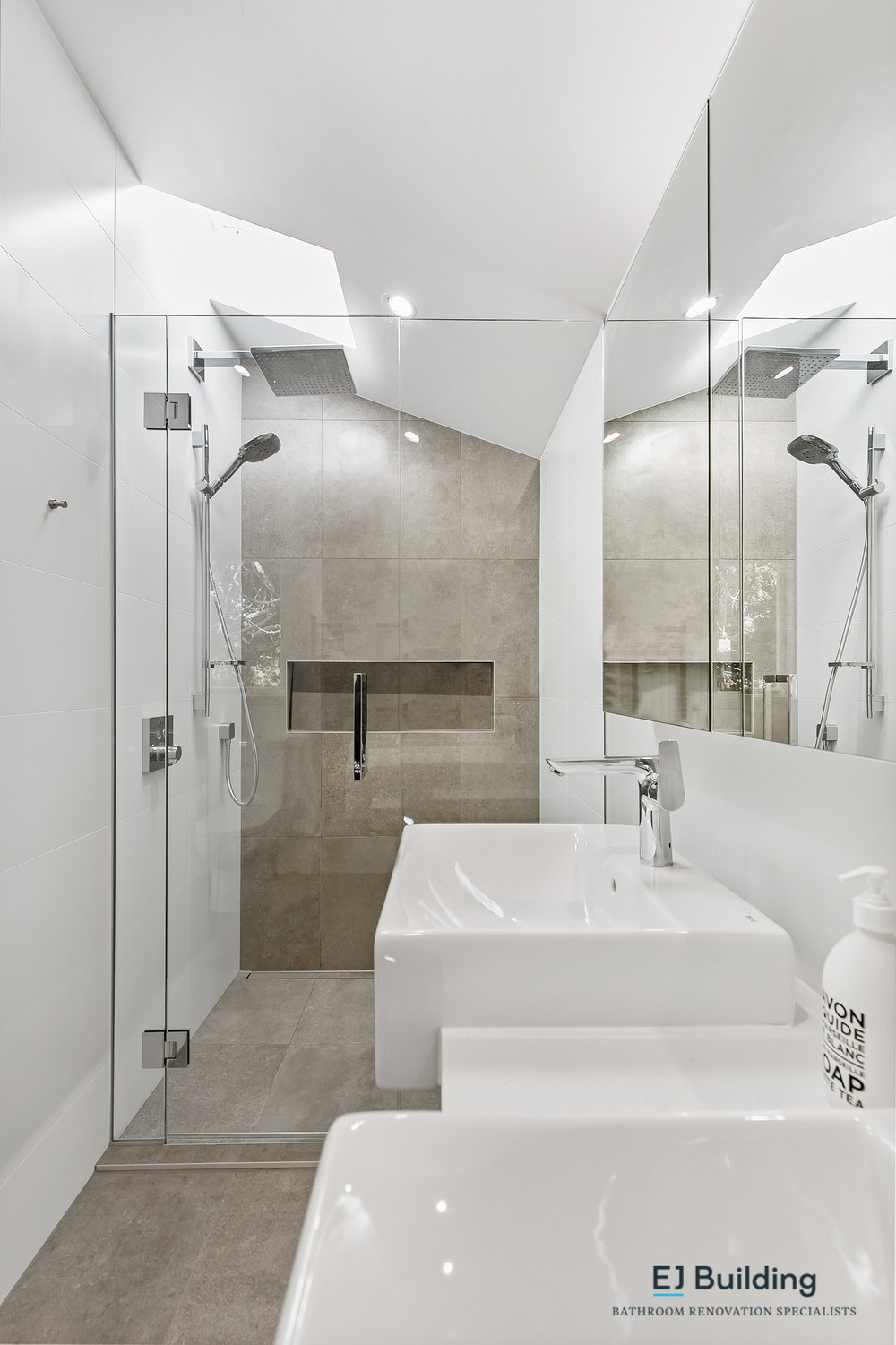 Ellerslie bathroom renovator Auckland. Bathroom renovation ideas with large wall to wall shower and skylight above. Double vanity with matching mirror cabinet . Bathroom Renovation by E J Building Bathroom renovators In Auckland.
