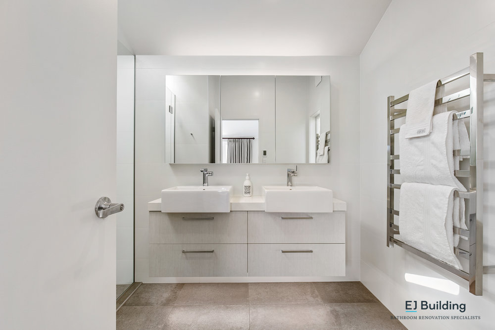 Ellerslie bathroom renovator Auckland. Led light above mirror cabinet and below vanity. Under tile heating with large heated towel rail . Bathroom Renovation by E J Building Bathroom renovators In Auckland.