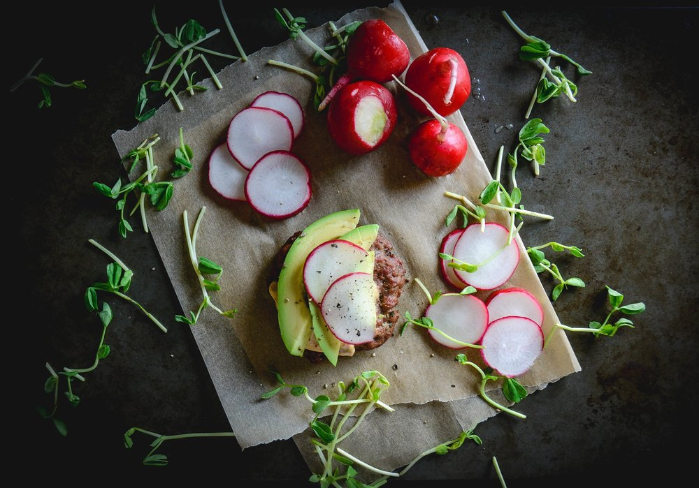 pub burger with avocado radishes and greens